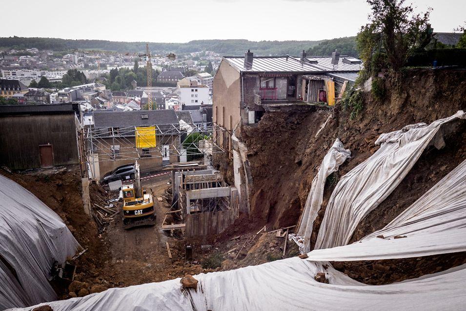 Le jardin de la maison qui jouxte le chantier, à droite, a été recouvert de gravats lors du glissement de terrain. Le sol où se trouvent les fondations de la maison s'est partiellement effondré. Une partie du jardin des Ribeiro a aussi été recouverte.