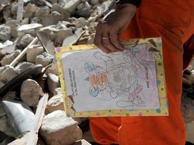 Ein niederländische Helfer mit einer in den Trümmerbergen von Port-au-Prince gefundenen Kinderzeichnung.