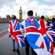 TOPSHOT - People walk over Westminster Bridge wrapped in Union flags, towards the Queen Elizabeth Tower (Big Ben) and The Houses of Parliament in central London on June 26, 2016.  Britain's opposition Labour party plunged into turmoil Sunday and the prospect of Scottish independence drew closer, ahead of a showdown with EU leaders over the country's seismic vote to leave the bloc. Two days after Prime Minister David Cameron resigned over his failure to keep Britain in the European Union, Labour leader Jeremy Corbyn faced a revolt by his lawmakers who called for him, too, to quit.  / AFP PHOTO / Odd ANDERSEN