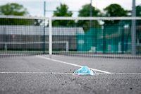 Eine Wegwerfschutzmaske liegt auf einem gesperrten Tennisplatz/ Sport, 2020 / 03.05.2020 /Sportplaetze während der Corona-Zeit / TC Lorentzweiler, Lorentzweiler /Foto: Ben Majerus