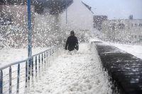 16.02.2020, Frankreich, Saint-Gu�nol�: Eine Person geht auf einem B�rgersteig durch Meeresschaum, der von Sturm �Dennis� an Land gesp�lt wurde. Foto: Fred Tanneau/AFP/dpa +++ dpa-Bildfunk +++