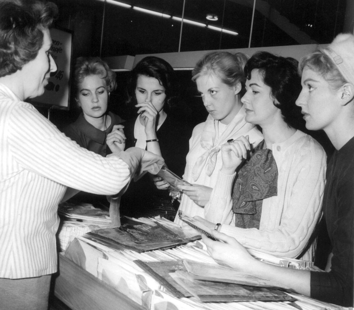1957: Die fünf Schönheitsköniginnen des Jahres,  Miss England, Miss Australien, Miss Europa, Miss Frankreich und Miss Schweden, die damals als Mannequins durch Deutschland reisten, suchen sich die passenden Damenstrümpfe aus. Am 15. Mai 1940 kam es vor Kaufhäusern sogar noch zu tumultartigen Zuständen. Die Frauen rissen sich um die ersten in Massenproduktion hergestellten Strümpfe aus Nylon.