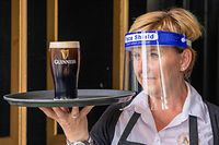 An employee wearing PPE (personal protective equipment), of a face shield or visor as a precautionary measure against spreading COVID-19, poses for a photograph with a customer's pint of Guinness at the re-opened Murray's Bar in Dublin on June 29, 2020, as lockdown measures begin to be eased. - Irish pubs unlock their doors and begin pouring pints on Monday, ending a 15-week dry spell forced by the nation's coronavirus lockdown. All domestic travel restrictions were also lifted, as churches, hairdressers, cinemas and museums opened and mass gatherings of 50 indoors or 200 outdoors were permitted. (Photo by Paul Faith / AFP)