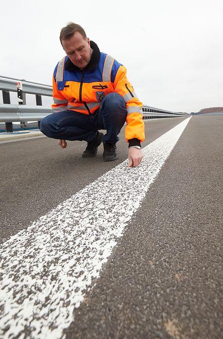 Christoph Schinhofen, Bauaufseher beim Landesbetrieb Mobilität Rheinland-Pfalz, begutachtet die soeben aufgebrachten Fahrbahnmarkierungen.