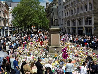 Crowds look at the balloons, flowers and messages of condolence left for the victims of the Manchester Arena attack, in central Manchester