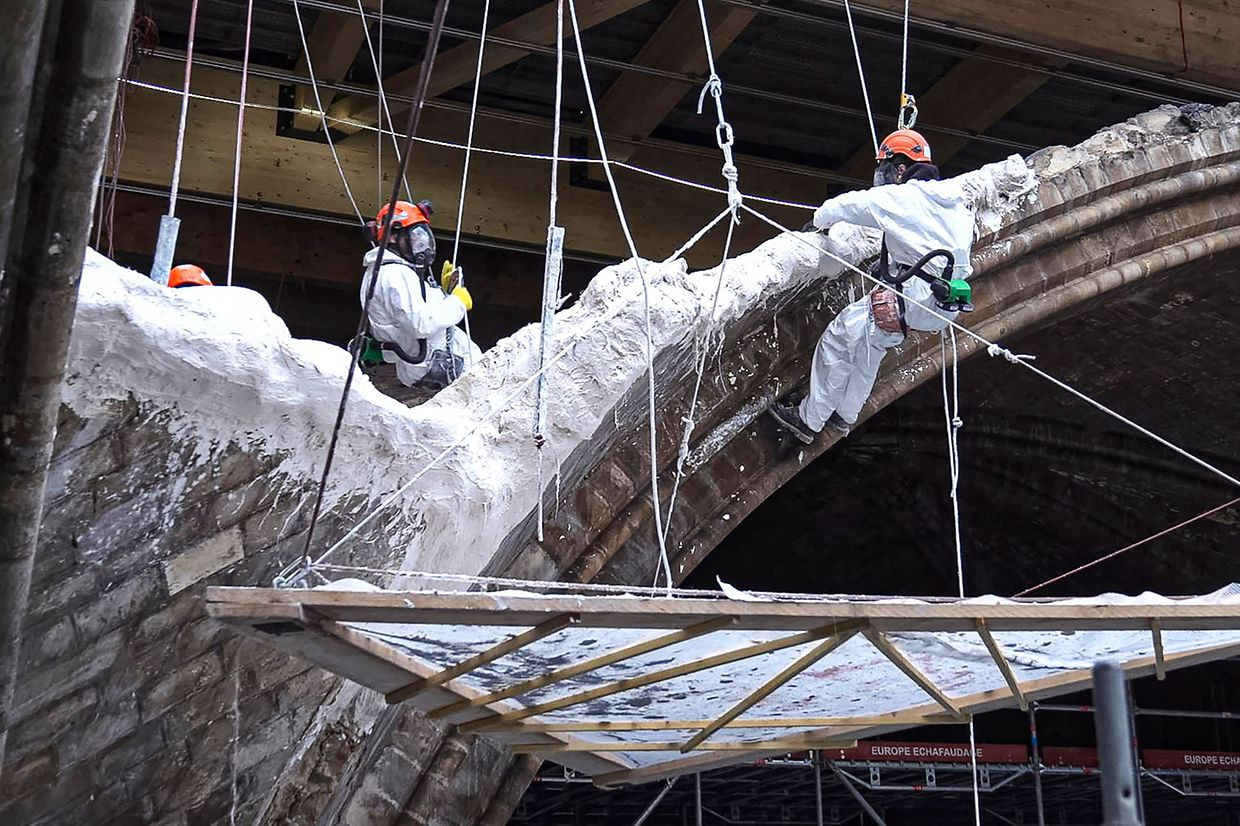 A grab from a video recorded by AFP on April 9, 2021 shows builders working on the restoration of the Notre-Dame Cathedral, in Paris, damaged by the April 15, 2019 fire. (Photo by Antoine BOUTHIER / AFP)