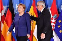 European Commission President Jean-Claude Juncker (R) speaks with German Chancellor Angela Merkel during an informal EU summit on migration issues at EU headquarters in Brussels, on June 24, 2018.   EU leaders headed to Brussels for emergency talks over migration as Italy's new populist cabinet turned away another rescue ship, vowing no longer to shoulder Europe's migrant burden. / AFP PHOTO / POOL / Geert Vanden Wijngaert