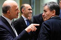 European Commissioner for Economic and Financial Affairs, Taxation and Customs Pierre Moscovici (L) talks with Greek Finance Minister Euclid Tsakalotos (R) at the start of an Eurogroup meeting at the EU headquarters in Brussels on December 3, 2018. (Photo by JOHN THYS / AFP)