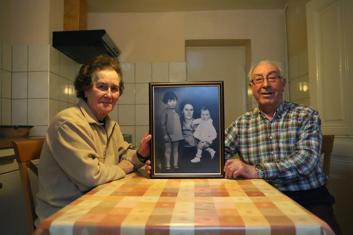 Le couple tient un portrait d'Isaura avec leurs deux filles