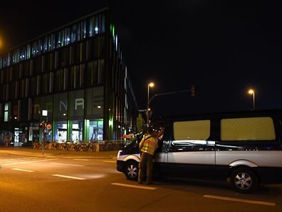 A funeral car arrive near the shopping mall the Olympia Einkaufzentrum (OEZ) in Munich on July 22, 2016 following a shooting earlier.  Elite German police were hunting for gunmen who went on a shooting rampage at a busy mall in Munich, killing eight people in cold blood in the third attack on civilians in Europe in barely a week. The southern city was in lockdown after the shootings, which saw panicked shoppers fleeing the Olympia mall as anti-terror police launched a massive operation to track down the assailants.  / AFP PHOTO / CHRISTOF STACHE