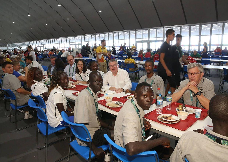IOC-Präsident Thomas Bach (weißes Hemd) hat am Montag das Flüchtlingsteam im Olympischen Dorf besucht. Rechts von ihm ist der Luxemburger Teilnehmer Yonas Kinde zu sehen.