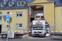 dpatopbilder - 21.10.2020, Rheinland-Pfalz, Trier: Ein Miet-LKW steckt in einer Hausdurchfahrt fest. Teile eines darüber gelegenen Mehrfamilienhauses sind dabei eingestürzt, verletzt wurde niemand. (zu dpa «Lkw fährt sich in Unterführung fest - Hausfassade teils eingestürzt») Foto: Harald Tittel/dpa +++ dpa-Bildfunk +++