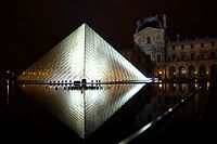 (FILES) In this file photo taken on October 02, 2018, the Louvre Pyramid is illuminated in the night, prior to the Louis Vuitton Spring-Summer 2019 Ready-to-Wear collection fashion show in Paris. - The world's most popular museum, the Paris Louvre, received over 10 million visitors in 2018, a record which it partly attributed Thursday to a Beyonce video shot against the backdrop of the Mona Lisa and other famous works. (Photo by Bertrand GUAY / AFP)