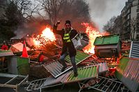 "TOPSHOT - A yellow vest ""Gilets Jaunes"" anti-government protestor stands on a burning barricade in Paris on January 5, 2019 during clashes with security personnel. - France's ""yellow vest"" protestors were back on the streets again as a government spokesman denounced those still protesting as hard-liners who wanted only to bring down the government. Several hundred protestors gathered on the Champs Elysees in central Paris, where around 15 police wagons were also deployed, an AFP journalist said. Marches were underway in several other cities across France. (Photo by Zakaria ABDELKAFI / AFP)"