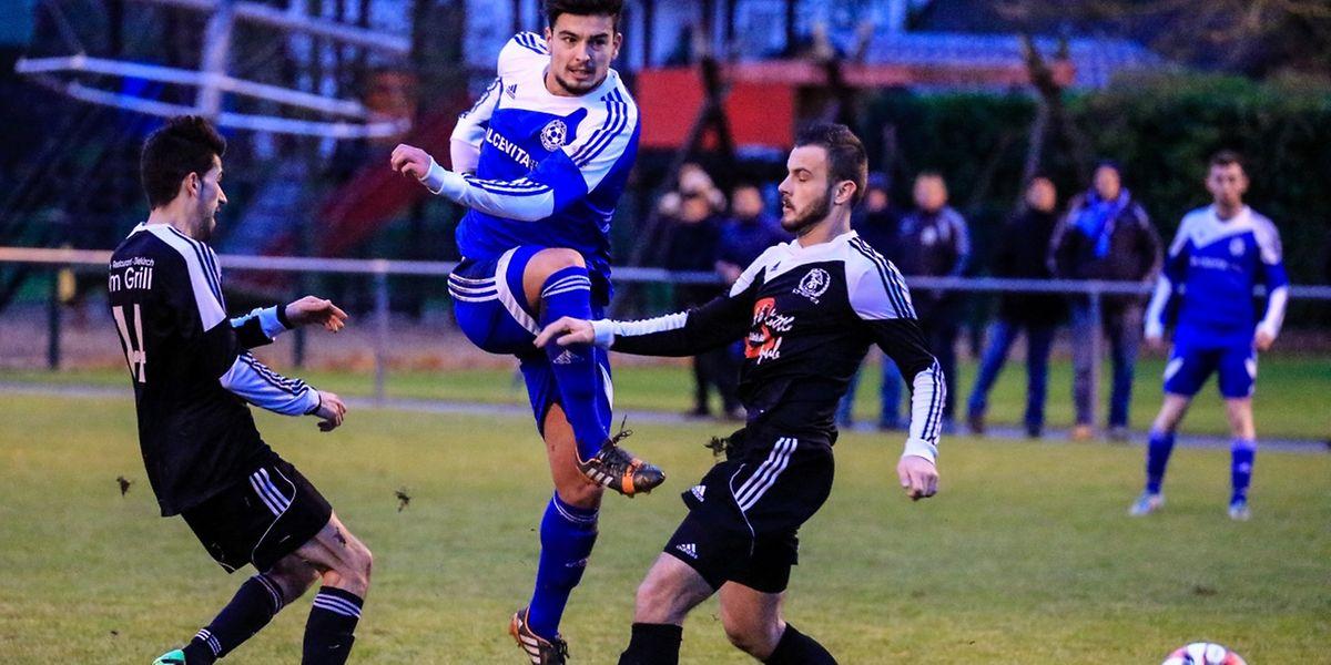 Almin Kocan (US Boevange, en bleu) tente sa chance au but, malgré la double présence de Joao Moreiro et Edwin Muratovic (Gilsdorf)