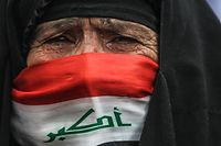 TOPSHOT - An elderly Iraqi woman, her face covered with a national flag, cries as she watches anti-government demonstrators protesting in the capital Baghdad's Tahrir square, on January 10, 2020. - Thousands of Iraqis rallied across the country today, reviving a months-long protest movement against the government and adding criticisms of both the US and Iran to their chants. (Photo by AHMAD AL-RUBAYE / AFP)
