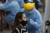 ARCHIV - 22.12.2020, Peru, Lima: Ein Medizinischer Mitarbeiter in Schutzkleidung nimmt einen Nasenabstrich bei einer Patientin, um sie auf das Coronavirus zu testen. Auch nach einer Veröffentlichung aus Japan sieht ein deutscher Immunologe in der sogenannten Lambda-Variante des Coronavirus noch keinen Grund zur Besorgnis. (zu dpa «Immunologe: Daten zu Lambda-Variante noch nicht beunruhigend») Foto: El Comercio/GDA via ZUMA Wire/dpa +++ dpa-Bildfunk +++