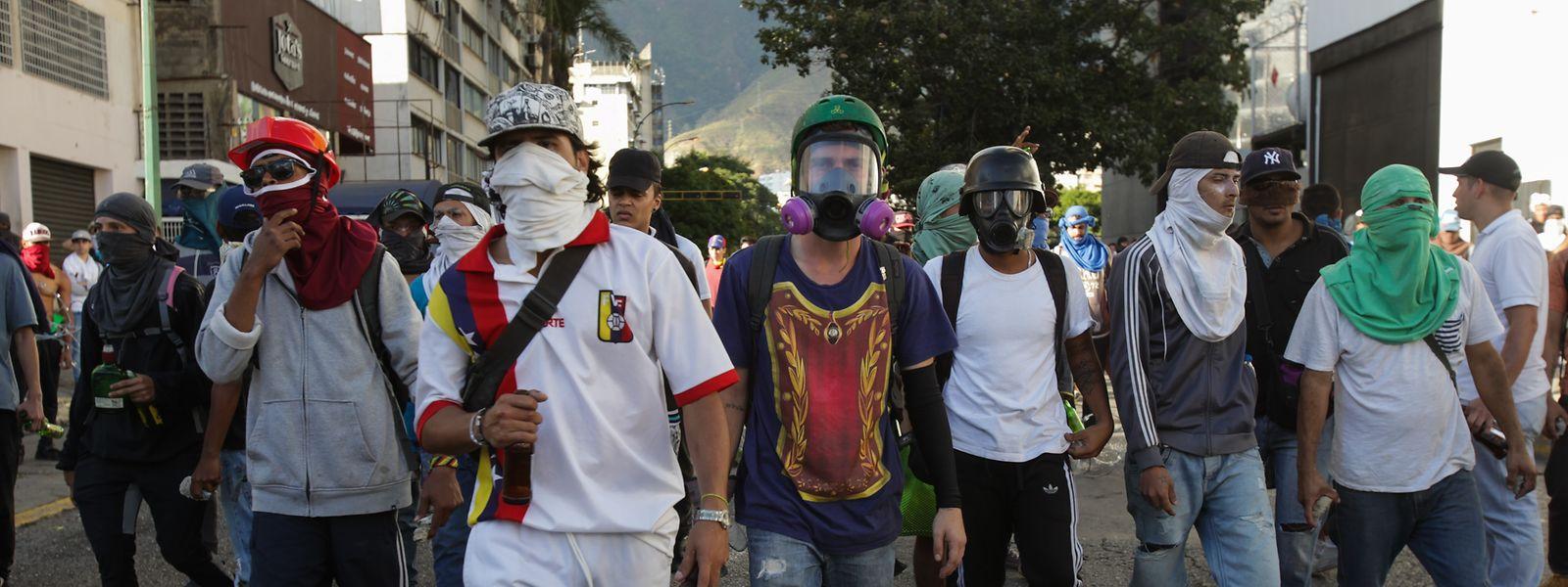 Vermummte und maskierte Menschen protestieren gegen den venezolanischen Präsidenten Maduro.