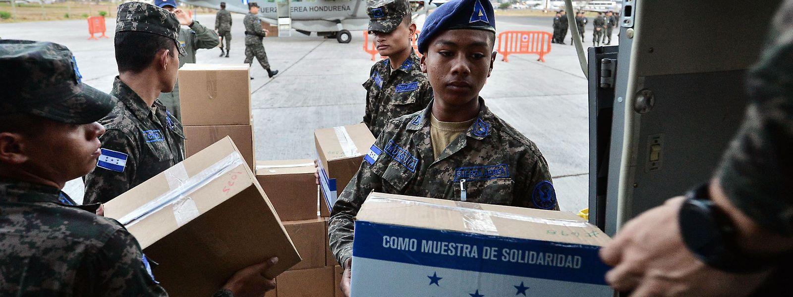 Mitglieder der Luftmacht aus Honduras laden Hilfsgüter für Venezuela in Flugzeuge.