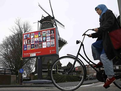 A woman cycles past an election poster billboard and a windmill in Amsterdam