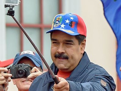 Venezuelan President Nicolas Maduro makes a selfie during a march to mark International Workers' Day, in Caracas on May 1, 2016