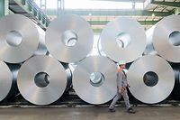 ARCHIV - 13.07.2020, Niedersachsen, Salzgitter: Ein Mitarbeiter geht bei der Salzgitter AG an aufgewickeltem Stahl (Coils) vorbei. Salzgitter AG gibt am 11.08.2021 die Halbjahreszahlen bekannt. Foto: Hilal Özcan/dpa +++ dpa-Bildfunk +++