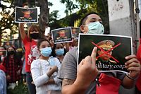 A Myanmar migrant holds up a poster with the image of Myanmar's Chief Senior General Min Aung Hlaing, commander-in-chief of the Myanmar armed forces, as they take part in a demonstration outside the Myanmar embassy in Bangkok on February 1, 2021, after Myanmar's military detained the country's de facto leader Aung San Suu Kyi and the country's president in a coup. (Photo by Lillian SUWANRUMPHA / AFP)
