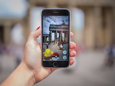 A woman points her smart phone at the Brandenburg Gate as she plays the Pokemon Go mobile game in Berlin on July 13, 2016. The Pokemon Go mobile gaming craze reached European fans with players in Germany the first to get their hands on the augmented reality sensation. / AFP PHOTO / dpa / Sophia Kembowski / Germany OUT