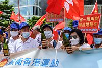 Pro-China supporters display Chinese and Hong Kong flags as they open champagne bottles during a rally near the government headquarters in Hong Kong on June 30, 2020, as China passed a sweeping national security law for the city. - China passed a sweeping national security law for Hong Kong, a historic move that critics and many western governments fear will smother the finance hub's freedoms and hollow out its autonomy. (Photo by Anthony WALLACE / AFP)