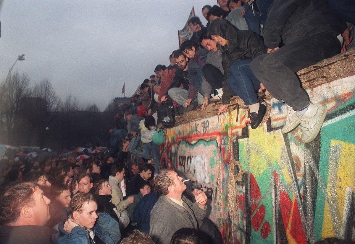 Dezember 1989: Ost-Berliner grüßen West-Berliner Bürger am Brandenburger Tor. Im August 1961 hatte die DDR damit begonnen, entlang der Grenze zu West-Deutschland und der Sektorengrenze innerhalb der Stadt Berlin eine Betonmauer zu errichten.
