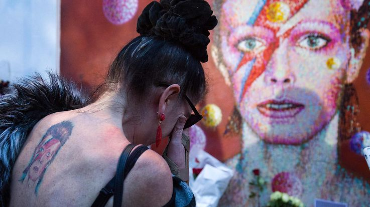 """TOPSHOT - A woman with a tatoo of David Bowie reacts as she pays her respects in front of the British singer, painted by Australian street artist James Cochran, aka Jimmy C, following the announcement of Bowie's death, in Brixton, south London, on January 11, 2016. British music icon David Bowie died of cancer at the age of 69, drawing an outpouring of tributes for the innovative star famed for groundbreaking hits like """"Ziggy Stardust"""" and his theatrical shape-shifting style.   AFP PHOTO / JUSTIN TALLIS  RESTRICTED TO EDITORIAL USE, MANDATORY MENTION OF THE ARTIST UPON PUBLICATION, TO ILLUSTRATE THE EVENT AS SPECIFIED IN THE CAPTION / AFP / JUSTIN TALLIS"""