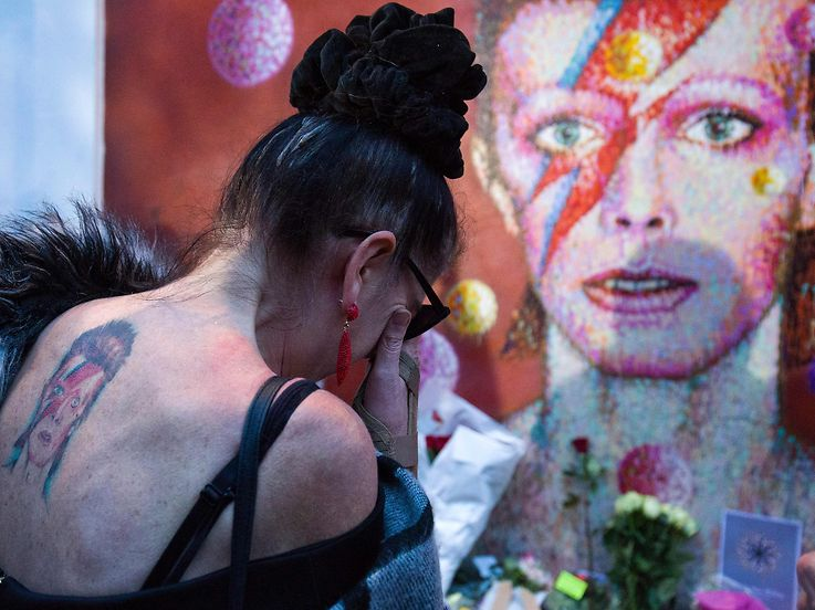 "TOPSHOT - A woman with a tatoo of David Bowie reacts as she pays her respects in front of the British singer, painted by Australian street artist James Cochran, aka Jimmy C, following the announcement of Bowie's death, in Brixton, south London, on January 11, 2016. British music icon David Bowie died of cancer at the age of 69, drawing an outpouring of tributes for the innovative star famed for groundbreaking hits like ""Ziggy Stardust"" and his theatrical shape-shifting style.   AFP PHOTO / JUSTIN TALLIS  RESTRICTED TO EDITORIAL USE, MANDATORY MENTION OF THE ARTIST UPON PUBLICATION, TO ILLUSTRATE THE EVENT AS SPECIFIED IN THE CAPTION / AFP / JUSTIN TALLIS"