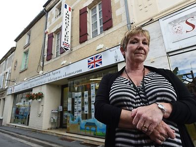 Real estate agent Terrie Simpson poses outside her estate agency dedicated to British buyers, in Eymet, southwestern France