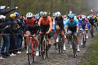 (FILES) In this file photograph taken on April 14, 2019, the pack ride on the Trouee d'Arenberg cobbled stones sector (19) during the 117th edition of the Paris-Roubaix one-day classic cycling race, between Compiegne and Roubaix, near Wallers, northern France. - A revised cycling calendar from the International Cycling Union on May 5, 2020, has revealed that the Giro d'Italia and Vuelta a Espana will overlap by six days, while there was also a brand new women's version of the sports toughest one day race. The 'Hell of the North' Paris-Roubaix has been fixed for October 25, with a first ever women's version of the gruelling, mud-splattered slog over cobbled mining roads. (Photo by Anne-Christine POUJOULAT / AFP)