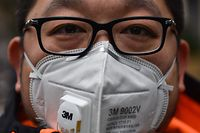 A man wearing a protective mask looks on while visiting the Jing'an temple in Shanghai on January 22, 2020. - A new virus that has killed nine people, infected hundreds and already reached the United States could mutate and spread, China warned January 22, as authorities scrambled to contain the disease during the Lunar New Year travel season. (Photo by HECTOR RETAMAL / AFP)