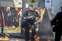 TOPSHOT - A riot police officer is reached by a petrol bomb during clashes with demonstrators protesting against police brutality in Medellin, Colombia on September 10, 2020. - At least 10 people were killed and hundreds wounded after rioting broke out in the Colombian capital Bogota during protests over the death of a man repeatedly tasered by police, authorities said Thursday. (Photo by JOAQUIN SARMIENTO / AFP)
