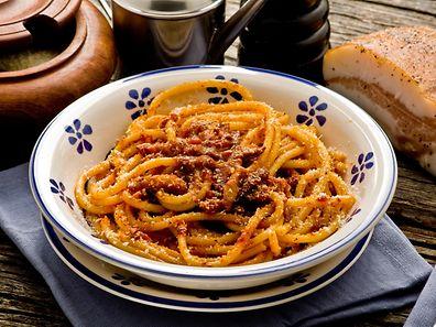 """Une belle assiette de """"bucatini a l'amatriciana"""" saupoudrée de parmesan. En haut à droite, le """"guanciale"""", qui ressemble (de vue) à du lard."""
