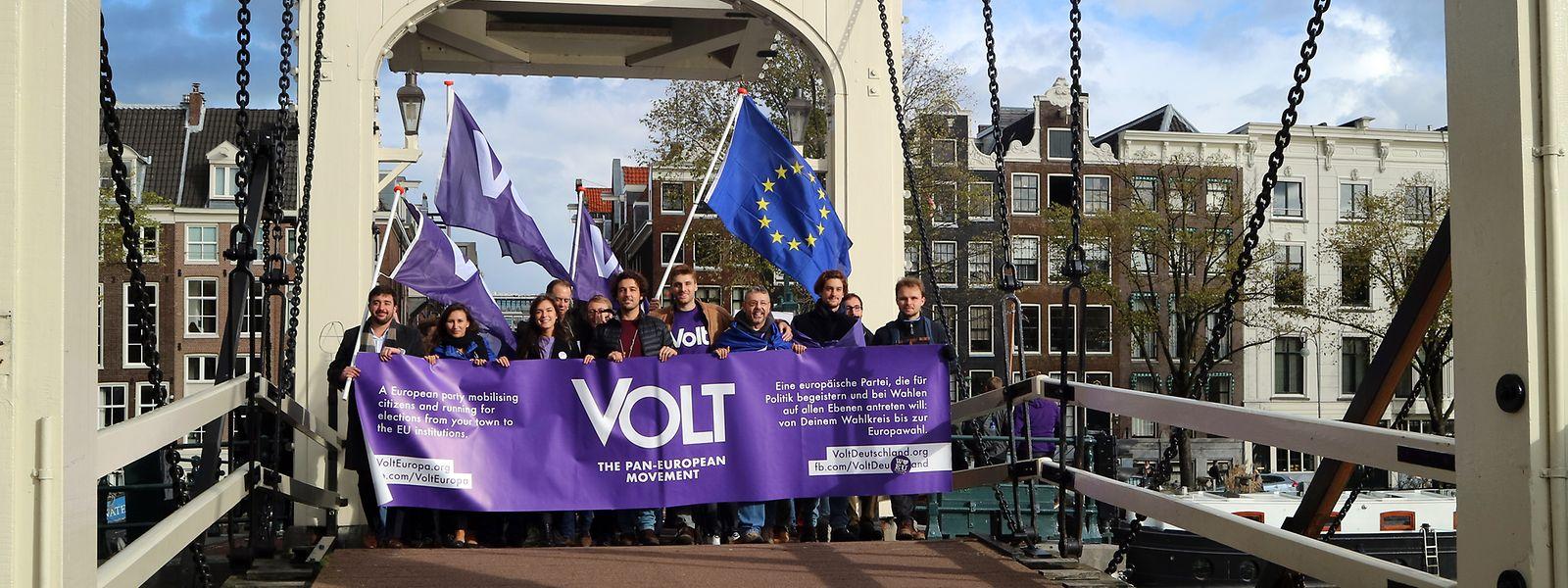 Mitglieder der proeuropäischen Partei Volt laufen in Amsterdam über eine Brücke.