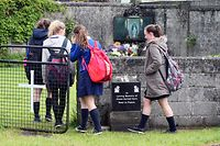 "(FILES) This file photo taken on June 09, 2014 shows schoolchildren arrive at a shrine in Tuam, County Galway on June 9, 2014, erected in memory of up to 800 children who were allegedly buried at the site of the former home for unmarried mothers run by nuns.  ""Significant quantities"" of baby remains have been discovered in an apparent makeshift crypt at the site of a former Catholic home for unmarried mothers in Ireland, an official commission said on March 3, 2017. The find in the town of Tuam in western Ireland came during extensive excavations by the Commission on Mother and Baby Homes, which was set up following the first claims in 2014 of possible child burials at the site.  / AFP PHOTO / PAUL FAITH"