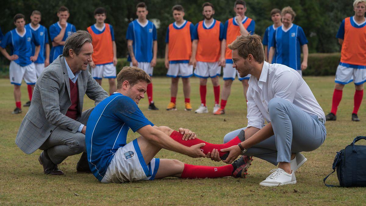 Bei einem Fußballspiel hat sich Marc (Joscha Kiefer) verletzt. Während Sam (Tommy Schlesser, r.) sich um den verletzten Knöchel kümmert, hofft William (Helmut Zierl, l.), dass die Verletzung nicht zu schwer ist.