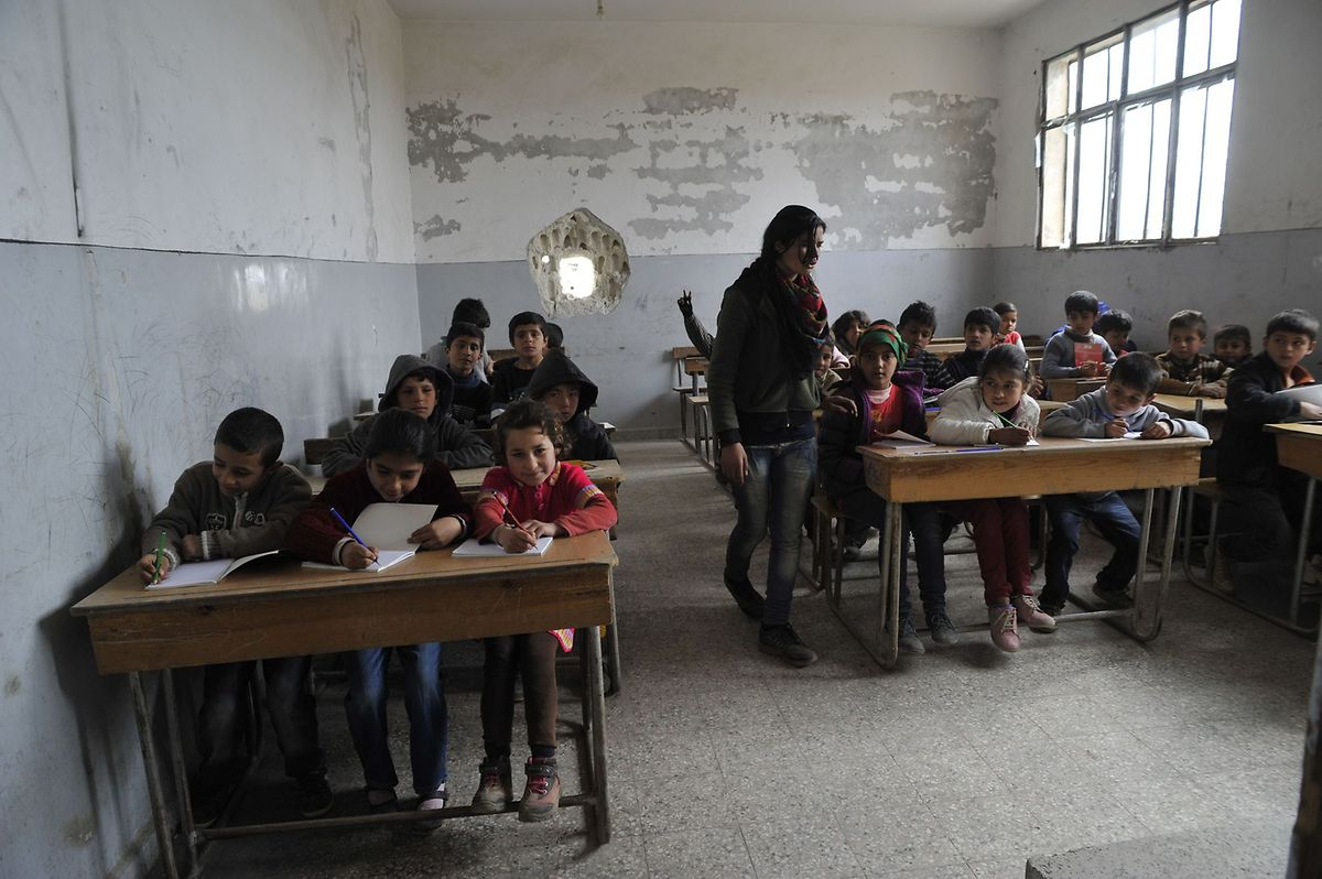 """Unterricht extrem. Keine Fenster und Einschusslöcher in den Wänden. Die Lehrer bemühen sich, den Kindern ein bisschen """"Schulalltag"""" zu vermitteln."""