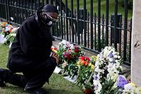 A man wearing a face covering bearing an image of Britain's Prince Philip, Duke of Edinburgh, pays his respects outside of Windsor Castle in Windsor, west of London, on April 16, 2021, following the April 9 death of the Prince at the age of 99. - Final preparations continued Friday in Britain for the funeral of Queen Elizabeth's husband Prince Philip, as it emerged that his grandsons Prince William and Prince Harry will not be side by side as the family walks into the chapel. (Photo by Tolga Akmen / AFP)