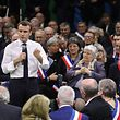 "French President Emmanuel Macron (L) gestures as he speaks during meeting gathering some 600 mayors who will relay the concerns aired by residents in their towns and villages in the Normandy city of Grand Bourgtheroulde on January 15, 2019, as part of the official launch of the ""great national debate"", a central plank of French President Emmanuel Macron bid to turn around his embattled presidency since the yellow vest (gilet jaune) movement protests. - The meeting sounds the start of two months of public consultations in towns and villages across the country on four main themes: taxation; France's transition to a low-carbon economy; democracy and citizenship, and the functioning of the state and public services. (Photo by Ludovic MARIN / AFP)"