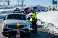 An officer of the Federal Police controls car drivers at the German-Czech border near Breitenau, eastern Germany, on February 14, 2021. - Germany implemented more measures to keep coronavirus variants at bay, banning travel from Czech border regions and Austria's Tyrol after a troubling surge in contagious mutations. (Photo by JENS SCHLUETER / AFP)