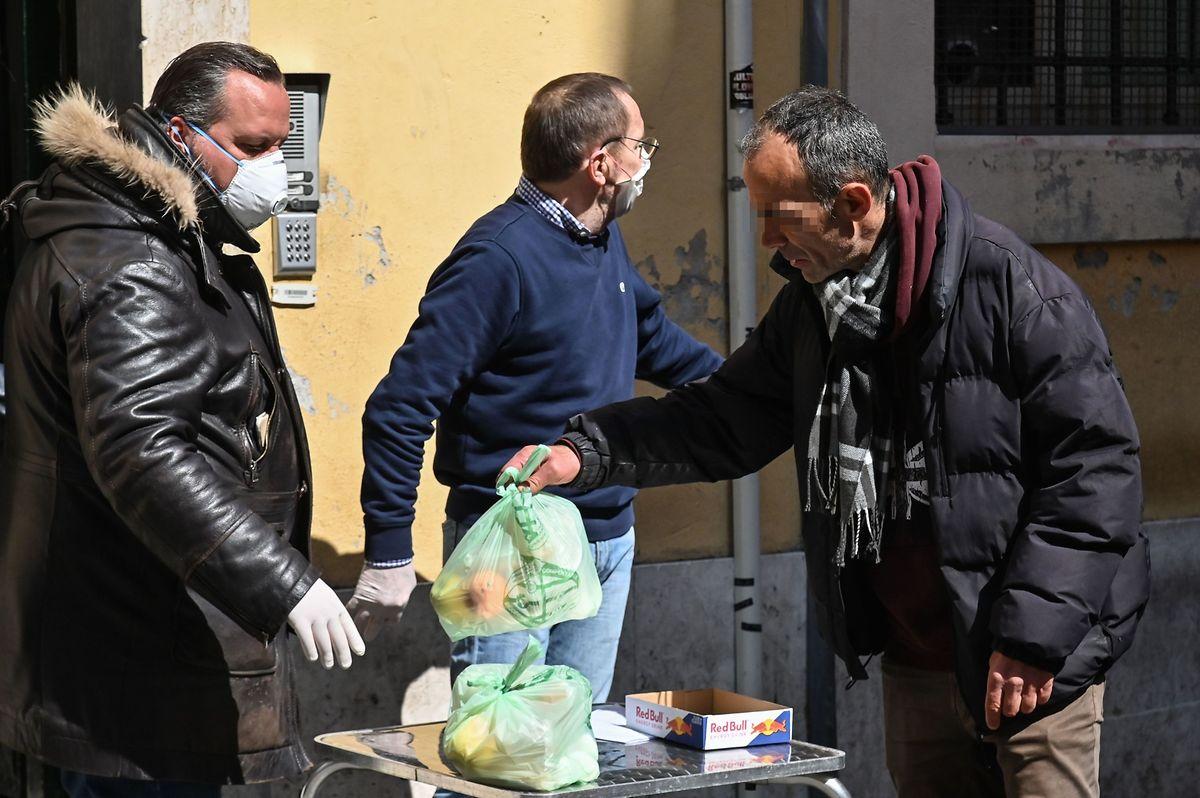Freiwillige von Hilfsorganisationen geben einem Obdachlosen im römischen Stadtteil Trastevere eine Tüte mit Lebensmitteln ab.
