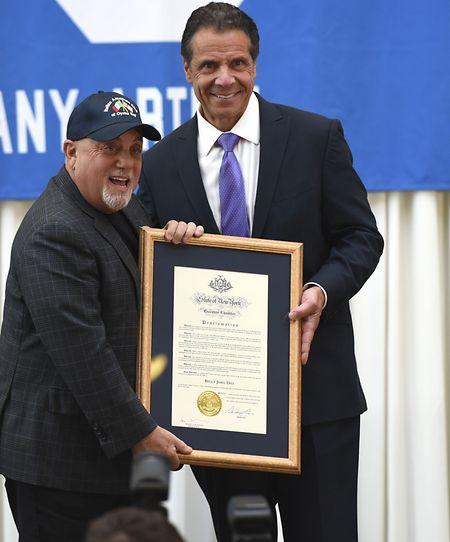 Billy Joel erhält aus den Händen von Gouverneur Andrew M. Cuomo eine Gedenkschrift.