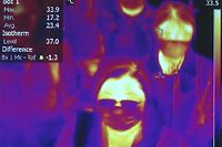 """TOPSHOT - This photo grabbed from a video taken and handout on January 23, 2020 by Rome's Fiumicino Airport Authority (ADR) shows passengers scanned by thermal imaging for body temperature as they go through  health measures and procedures against deadly SARS-like virus outbreak risks, after they landed at Rome's Fiumicino airport on a southern airlines flight from Wuhan, China. - China banned trains and planes from leaving a major city at the centre of a virus outbreak on January 23, seeking to seal off its 11 million people to contain the contagious disease that has claimed 17 lives, infected hundreds and spread to other countries. (Photo by Handout / AEROPORTO DI ROMA / AFP) / RESTRICTED TO EDITORIAL USE - MANDATORY CREDIT """"AFP PHOTO / ROME AIRPORT AUTHORITY / AEROPORTO DI ROMA"""" - NO MARKETING - NO ADVERTISING CAMPAIGNS - DISTRIBUTED AS A SERVICE TO CLIENTS"""