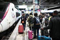 Passengers walk with their luggage before boarding a train at the Montparnasse rail station on April 3, 2021, as nationwide partial lockdown measures aimed at curbing the Covid-19 pandemic start today. - New restrictions come into force on April 3, 2021 in France, where authorities are scrambling to deal with a dramatic rise in Covid-19 cases that has overwhelmed hospitals in the capital Paris. (Photo by STEPHANE DE SAKUTIN / AFP)