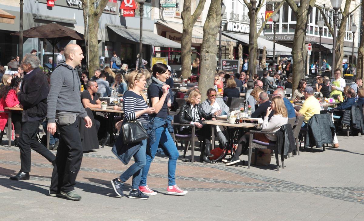 Mit aufgesetzten Sonnenbrillen genießen die Menschen die angenehmen Frühlingstemperaturen auf den Terrassen.