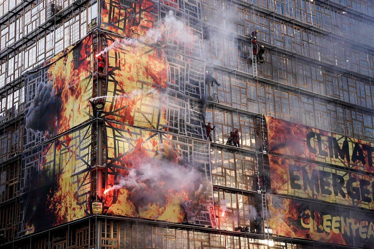 Greenpeace-Aktivisten kletterten am Donnerstagmorgen auf die Fassade des EU-Ratsgebäudes in Brüssel und entzündeten bengalische Feuer.